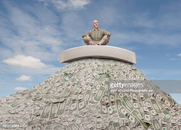 Caucasian businessman sitting on mattress on mountain of money