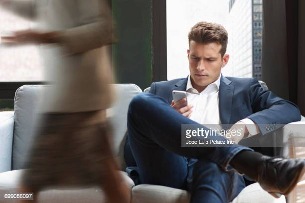 Caucasian businessman sitting on sofa texting on cell phone