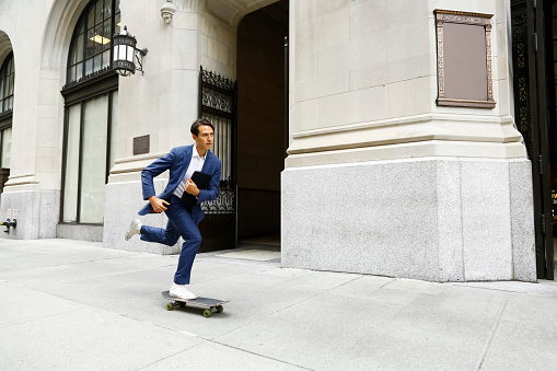 Caucasian businessman skateboarding on urban sidewalk - gettyimageskorea