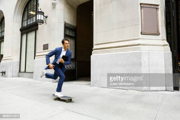 Caucasian businessman skateboarding on urban sidewalk