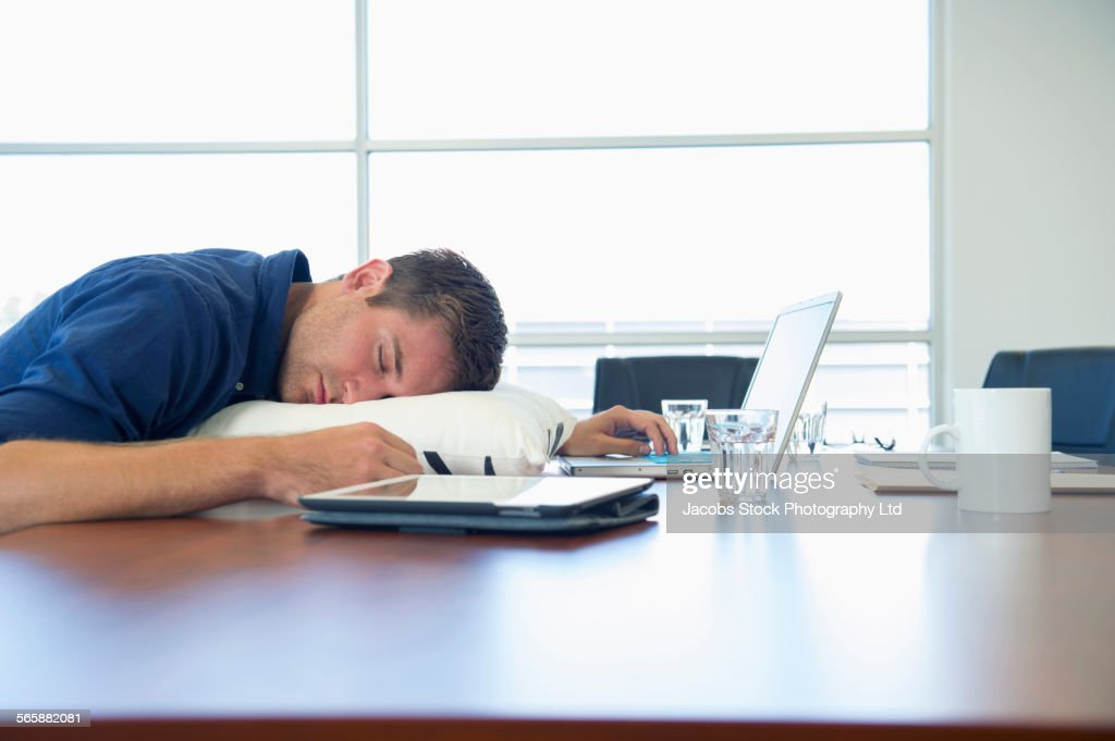 Caucasian businessman sleeping at conference table : Stock Photo