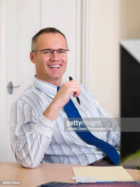 caucasian businessman smiling at desk in office - spalding england stock photos and pictures