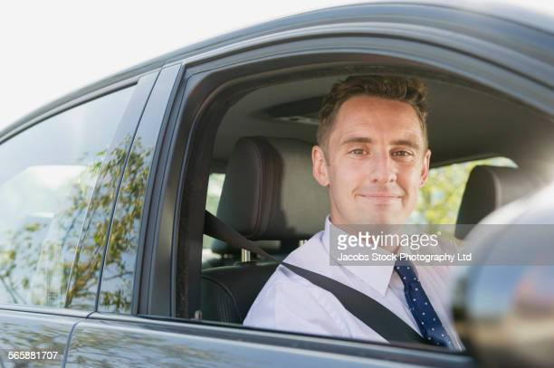 Caucasian businessman smiling in car window