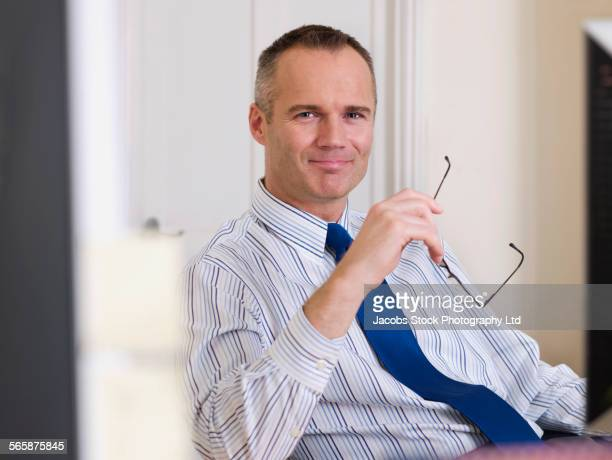 caucasian businessman smiling in office - spalding england stock photos and pictures