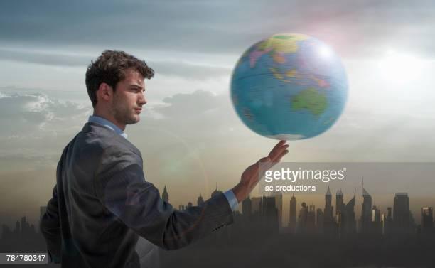 Caucasian businessman spinning globe on finger near city skyline