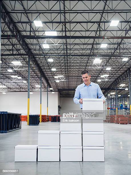 Caucasian businessman stacking boxes in warehouse