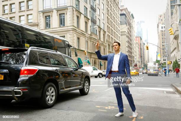 caucasian businessman standing in street hailing taxi - hail stock pictures, royalty-free photos & images