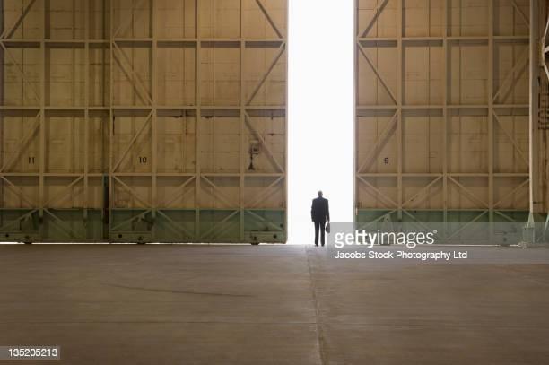 Caucasian businessman standing in warehouse doorway