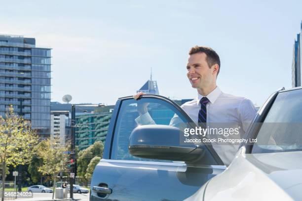 Caucasian businessman standing near open car door