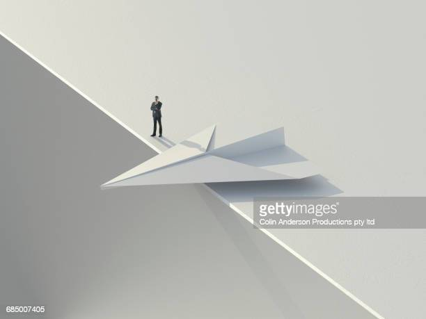 Caucasian businessman standing near paper airplane teetering on an edge