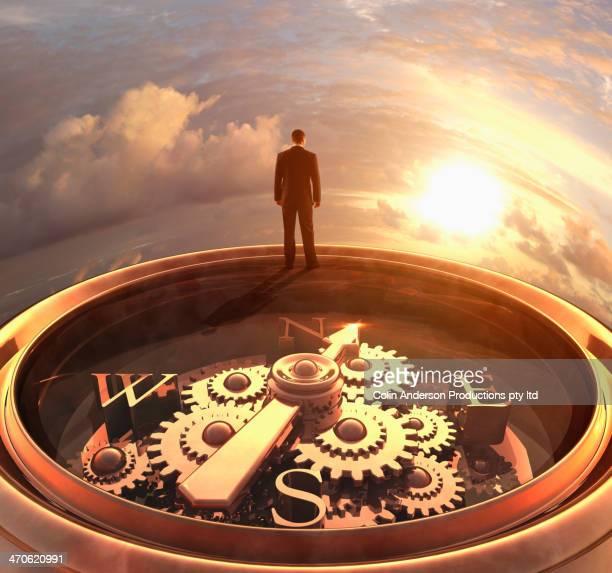 Caucasian businessman standing on compass