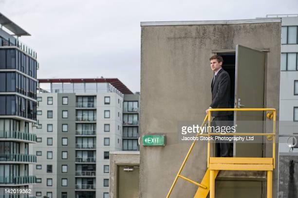 Caucasian businessman standing on rooftop