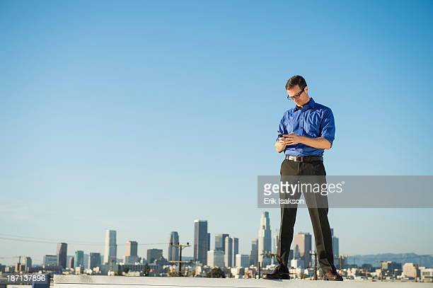 Caucasian businessman standing on urban rooftop