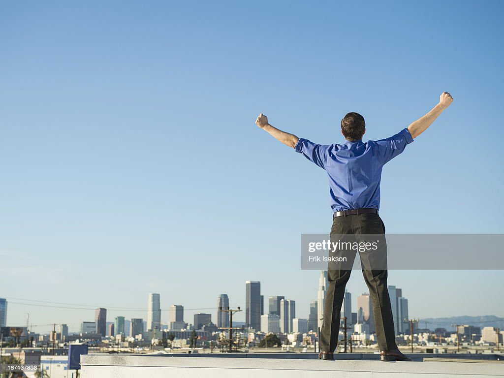 Caucasian businessman standing on urban rooftop : Stock Photo