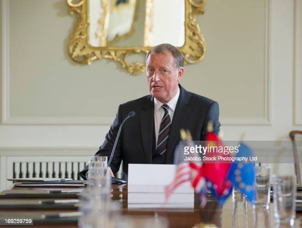 caucasian businessman talking in microphone - politician stock pictures, royalty-free photos & images