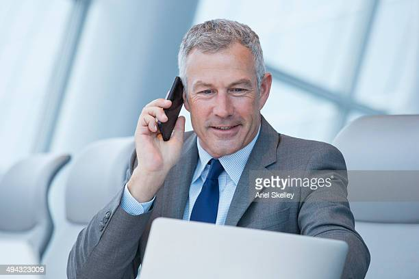 Caucasian businessman talking on cell phone at desk