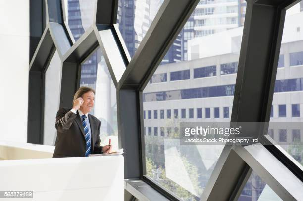 Caucasian businessman talking on cell phone at office window