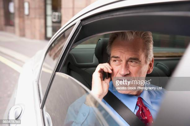 Caucasian businessman talking on cell phone in back seat of car