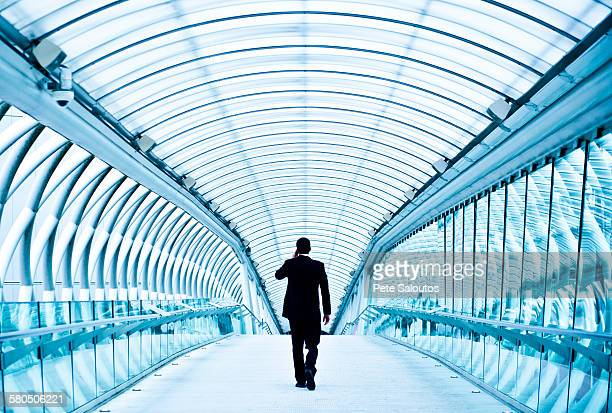 Caucasian businessman talking on cell phone in tunnel