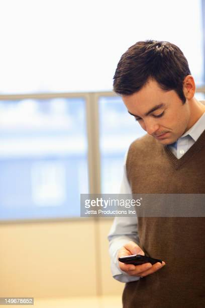 Caucasian businessman text messaging on cell phone in office