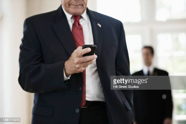 caucasian businessman text messaging on cell phone - politician stock pictures, royalty-free photos & images