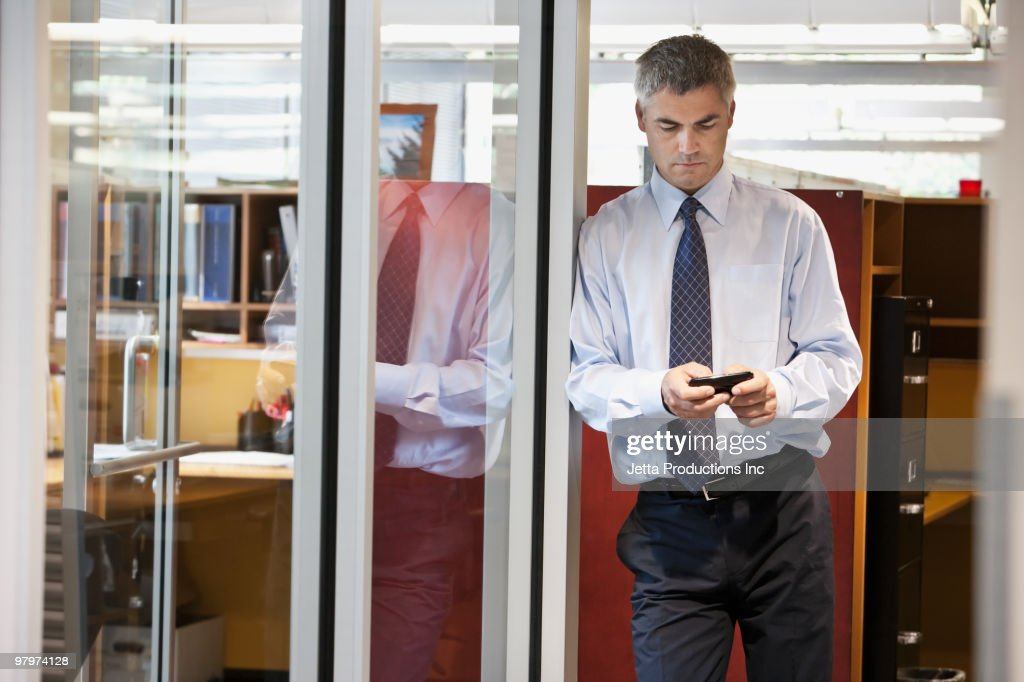 Caucasian businessman text messaging on cell phone : Stockfoto