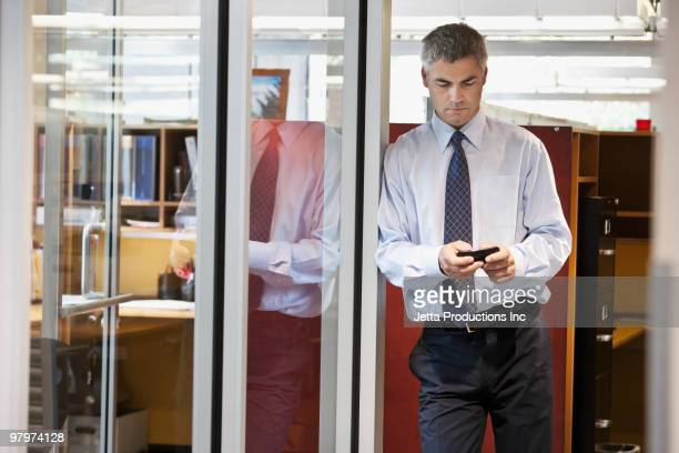 caucasian businessman text messaging on cell phone - elektronische organiser stockfoto's en -beelden