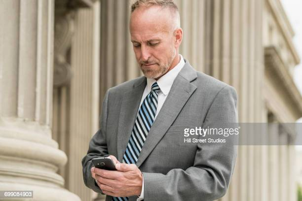 Caucasian businessman texting on cell phone outdoors