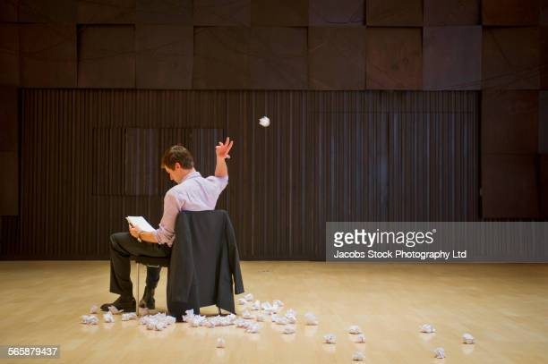 caucasian businessman tossing crumpled paperwork in barren room - lanciare foto e immagini stock