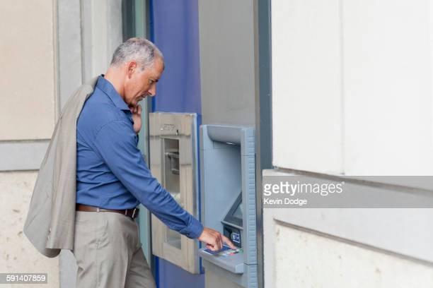 Caucasian businessman using ATM