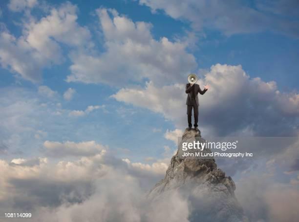 Caucasian businessman using bullhorn on mountain top