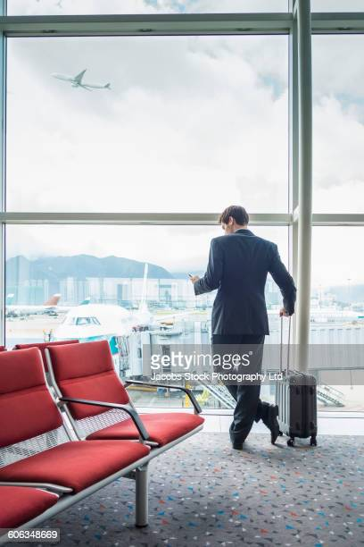 Caucasian businessman using cell phone in airport