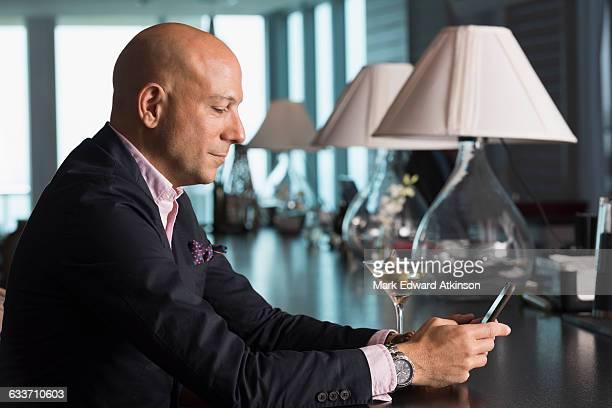 Caucasian businessman using cell phone in bar