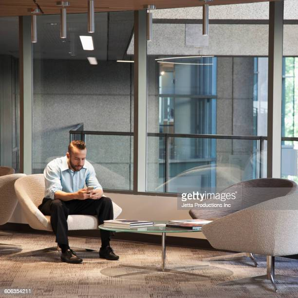 Caucasian businessman using cell phone in office lounge