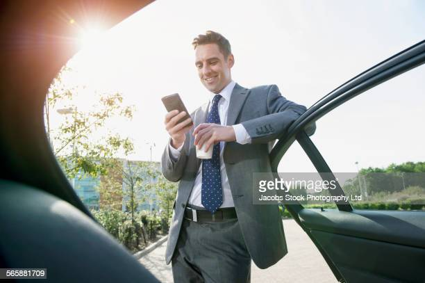 Caucasian businessman using cell phone near car