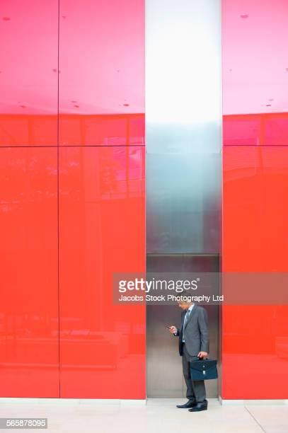 Caucasian businessman using cell phone near office elevator