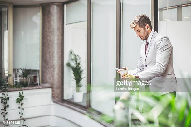 Caucasian businessman using cell phone on office balcony