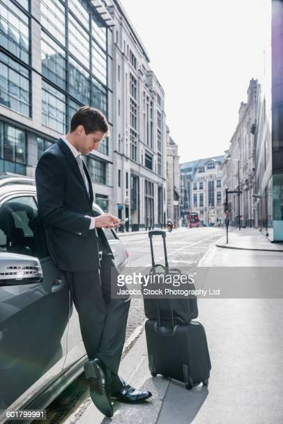Caucasian businessman using cell phone on sidewalk