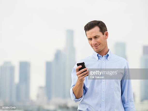 Caucasian businessman using cell phone on urban rooftop