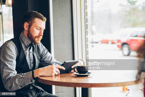 Caucasian businessman using digital tablet in cafe