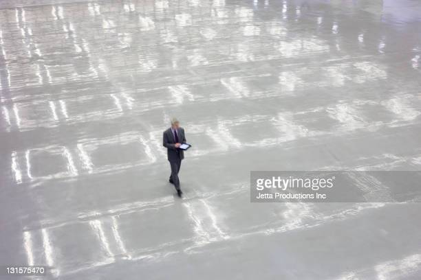 caucasian businessman using digital tablet in empty convention center - convention center stock pictures, royalty-free photos & images