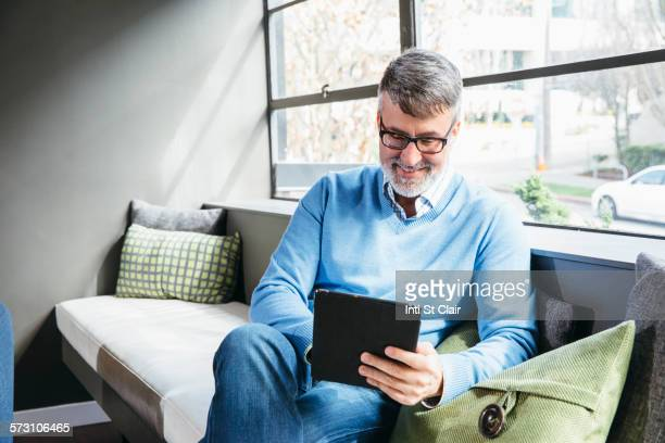 Caucasian businessman using digital tablet in office lobby