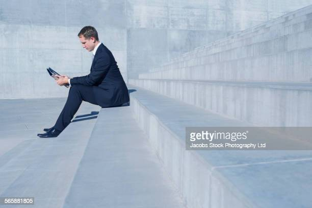 Caucasian businessman using digital tablet on outdoor staircase