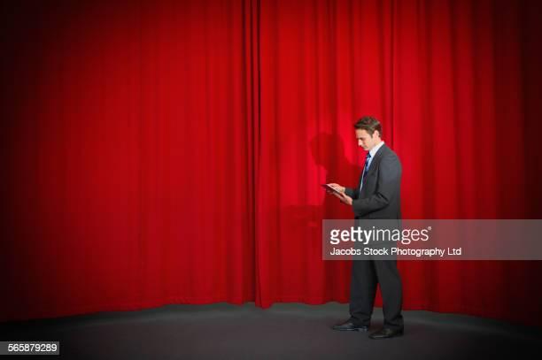 Caucasian businessman using digital tablet on stage
