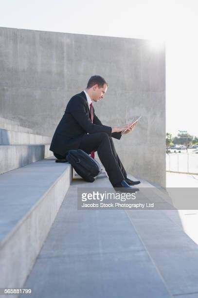 Caucasian businessman using digital tablet on staircase