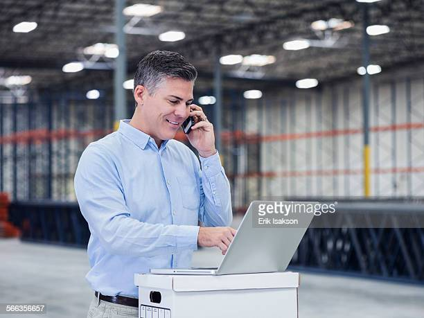 Caucasian businessman using laptop and cell phone in empty warehouse