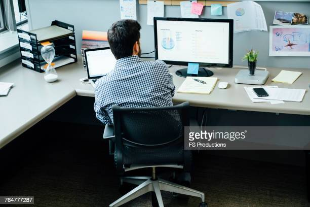 Caucasian businessman using laptop and computer in office