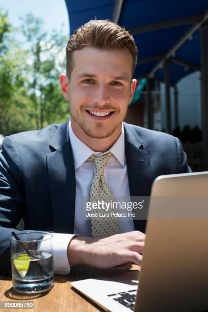 Caucasian businessman using laptop at cafe outdoors