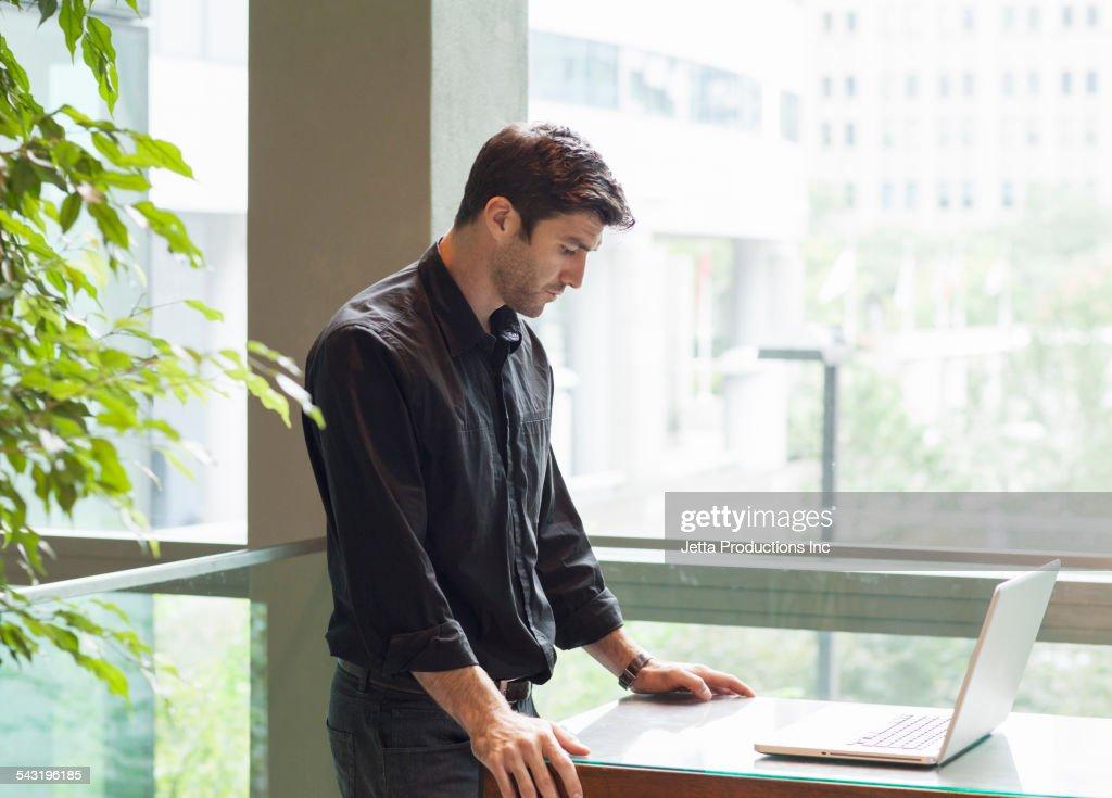Caucasian businessman using laptop at table : Stock Photo