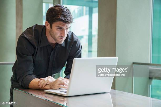 Caucasian businessman using laptop at table